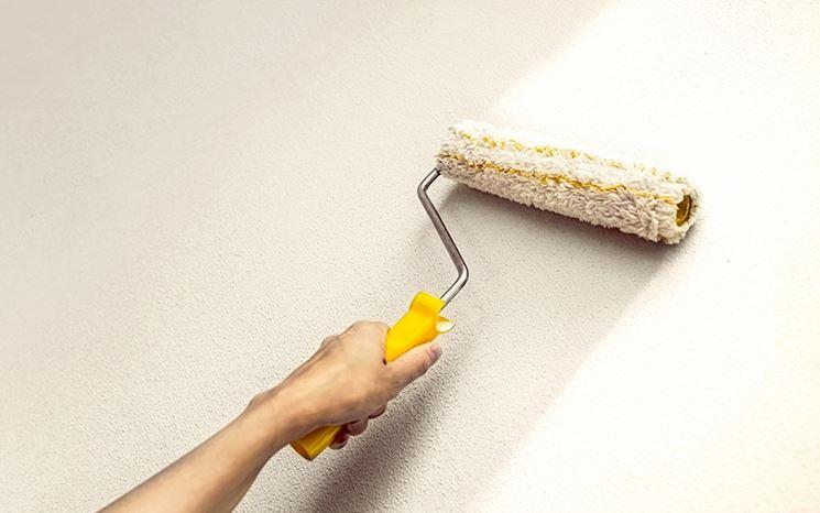 Un muro interno viene pitturato con un rullo
