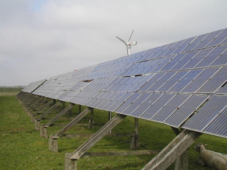 Campo con pannelli fotovoltaici e pala eolica per la produzione di energia verde