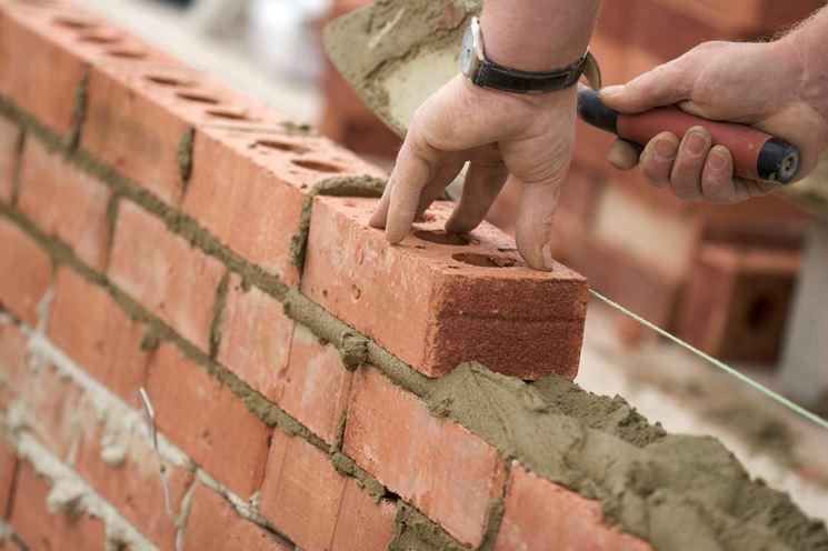 Operaio che ricostruisce un muro