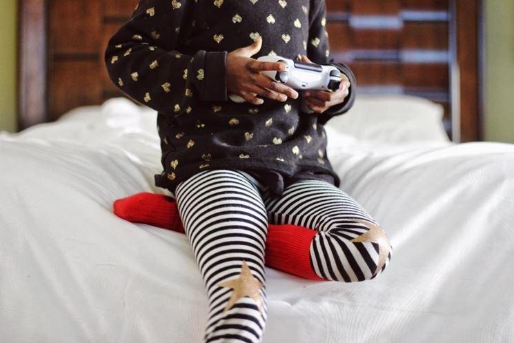 Bambina che gioca sul letto