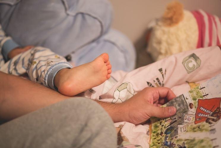 Genitore e bambino che leggono sul letto